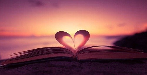 Heart from a book page against a beautiful sunset.